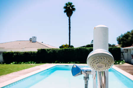 Shower head nozzle next to swimming pool with copy space Banco de Imagens