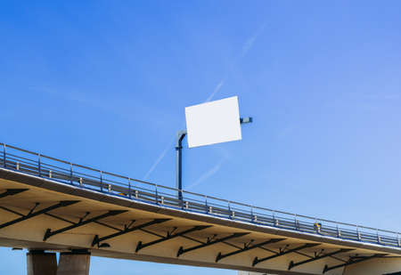 Large blank billboard at highway overpass with blue sky