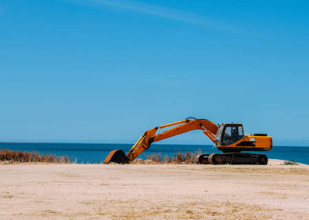 Yellow bulldozer working on a beach with copy space Banco de Imagens
