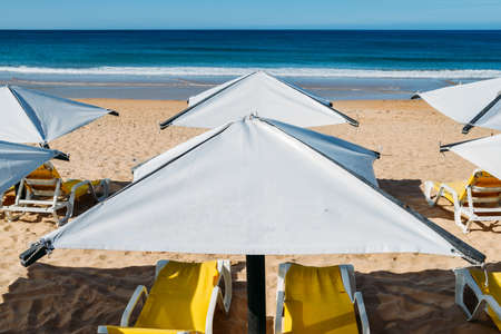 Sun loungers and a beach umbrella on a deserted beach perfect vacation concept