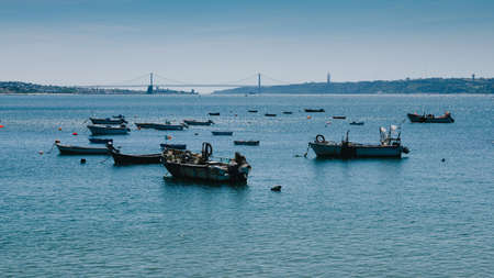 Small fishing boats on the Tagus overlooking the iconic 25 April Bridge, Lisbon, Portugal - Costa Verde Portuguese Riviera