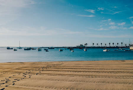 Empty sandy Praia do Ribeiro and boats on bay a a sunny summer morning. Cascais is a small quaint village 30km west of Lisbon Banco de Imagens