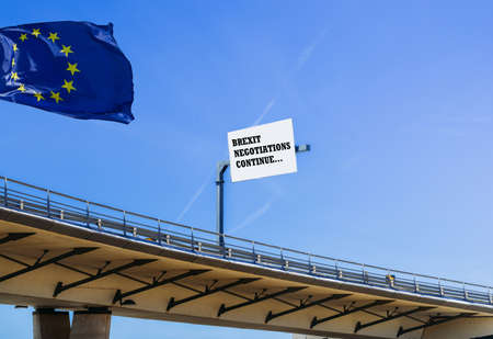 Large blank billboard at highway overpass with blue sky - Brexit message