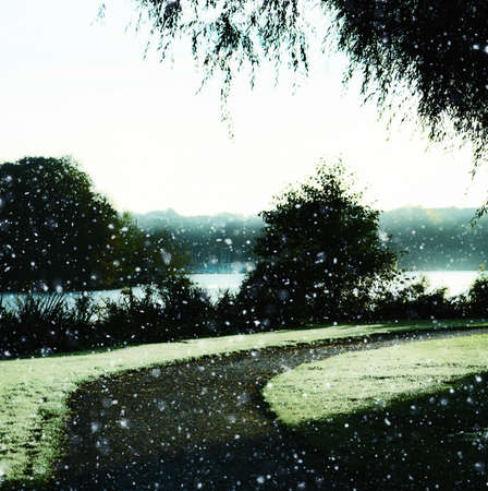 Empty footpath curving to right in park next to a lake while snowing in winter