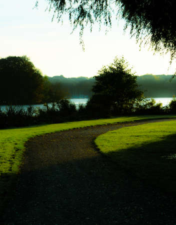 Empty footpath curving to right in park next to a lake in early spring