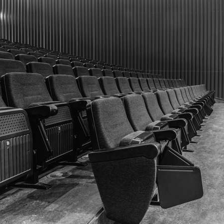 Selective perspective view towards empty audience seat in an indoor performance hall or cinema