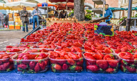Close up fresh red strawberry berries in plastic containers in wooden box on retail display of farmers market, high angle view Banco de Imagens
