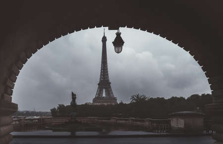 Eiffel Tower Paris uniquely framed by concrete arch of Bir-Hakeim Bridge - muted fine art colours Zdjęcie Seryjne - 129721109