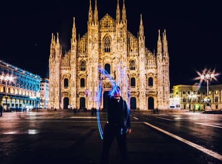 Man using light painting long exposure draws an M letter in front of the Milan Cathedral, Milan, Italy Stockfoto