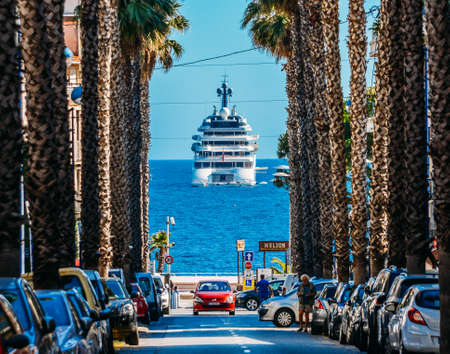 Palm tree lined boulevard leading to luxury yacht on ocean