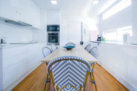 Stylish and brightly lit residential kitchen with dining table