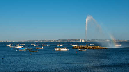 Geyser forming a rainbow on River Tagus with fishing boats overlooking 25 April Bridge and Rei Cristo statue in Lisbon, Portugal