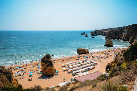 High perspective view of beachgoers at Cova Redonda Beach in Algarve, southern Portugal on a summer day