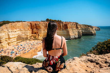 Young woman admiring view of cliffs, beach and turquoise ocean in Benagil beach, Algarve, Portugal