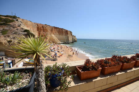 Beachgoers at Benagil beach, Algarve, Portugal during the summer