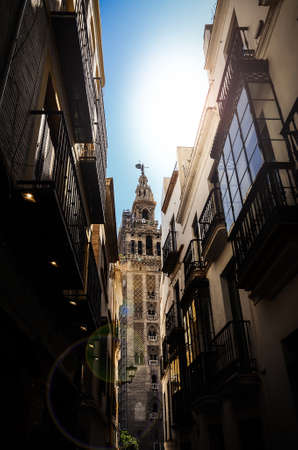 View of Giralda tower of Cathedral of Saint Mary of the See, Seville Cathedral, through a narrow street, Andalucia, Spain Фото со стока