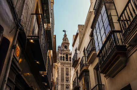 View of Giralda tower of Cathedral of Saint Mary of the See, Seville Cathedral, through a narrow street, Andalucia, Spain 免版税图像