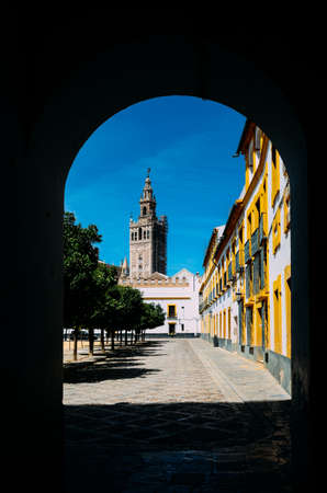 Seville Cathedrals Moorish Giralda tower as framed from a doorway at courtyard in Real Alcazar, Sevilla, Andalusia, Spain