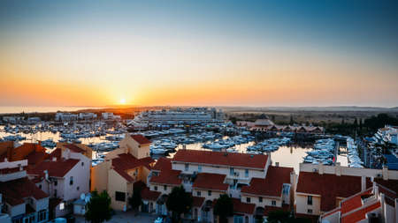 High perspective view of sunset at Vilamoura Marina, Algarve, Portugal with busy nightlife around the Marina full of shops and restaurants