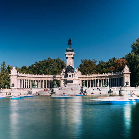 Long exposure of people on boats across from monument to Alfonso XII in the Parque del Buen Retiro, in Madrid, Spain Фото со стока