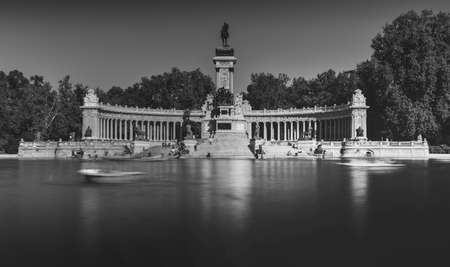 Monochrome long exposure of people on boats across from monument to Alfonso XII in the Parque del Buen Retiro, known as the Park of the Pleasant Retreat in Madrid, Spain Фото со стока