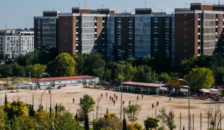 High perspective view of unidentifiable teenagers on a 11 a side amateur football match on a sandy patch in a residential neighbourhood 스톡 콘텐츠