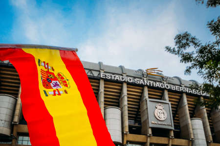 Madrid, Spain - Oct 26, 2019: Santiago Bernabeu Stadium of Real Madrid in Madrid, Spain. Spanish flag on foreground
