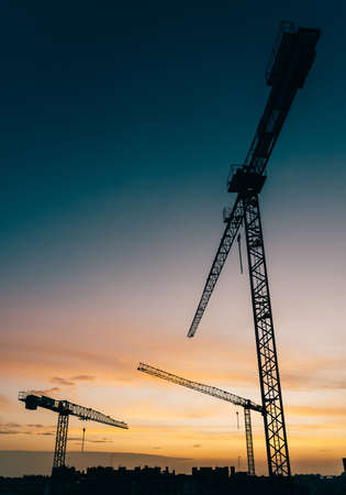 Backlit construction cranes at yard with copy space