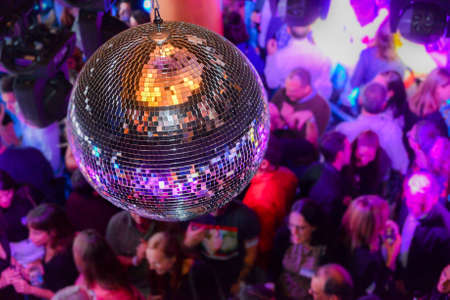 Disco ball with unidentifiable people in background within a nightclub