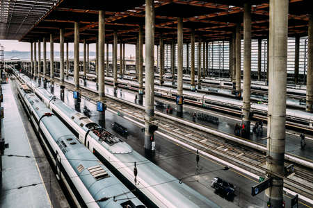 High perspective view of passengers and trains at Atocha, the the main railway station in Madrid, Spain