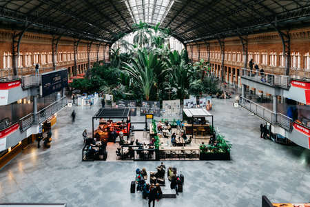 Original 19th century Atocha Railway Station in Madrid, Spain, is now a concourse with shops, cafes and a botanical garden forming the entrance to the new station 에디토리얼
