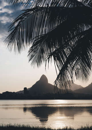 Morro Dois Irmaoes Mountain, translated into Portuguese as Two Brothers Mountain, as seen from Lagoa Rodrigo de Freitas at sunset in Rio de Janeiro, Brazil Фото со стока