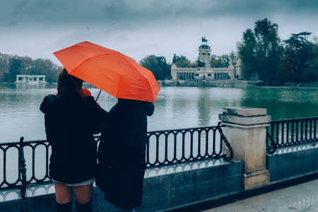 Two women admire the lake and monument to King Alfonso XII on a rainy winter day, Madrid, Spain