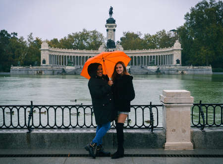Two women pose for a picture in front of the lake and monument to King Alfonso XII on a rainy winter day, Madrid, Spain