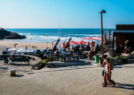 People relax at a cafe overlooking the golden Praia das Macas in Portugal on a sunny winter day