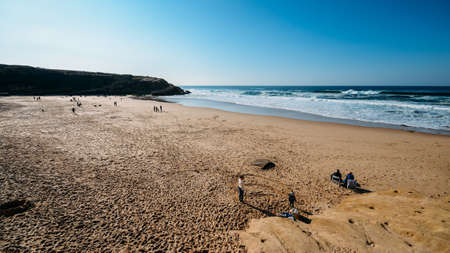 Families enjoy a relaxing afternoon at the golden Praia das Macas in Portugal on a sunny winter day