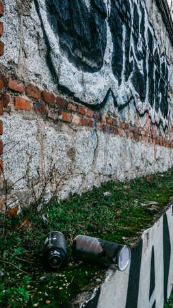 Aerosol spray cans next to wall covered in graffiti writing Editöryel