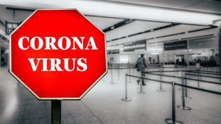 Coronavirus written on stop sign with passengers arriving at passport control within generic airport