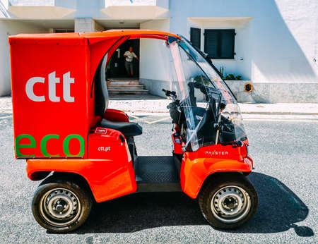 Red CTT electric mini car mail courier in Cascais, Portugal with mailman in background