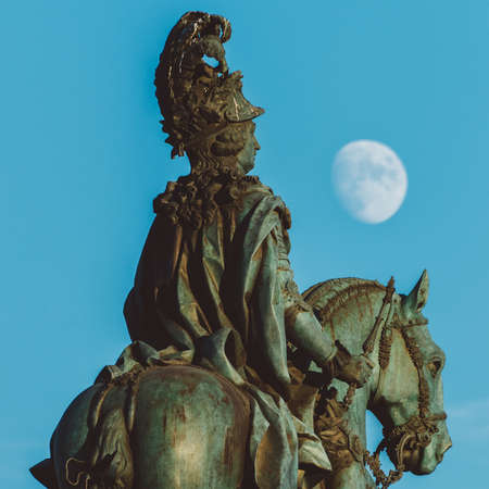 Equestrian statue of King John I in the Praca do Comercio in Lisbon, Portugal with a full moon