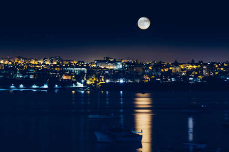 Night view of Cascais, Portugal with full moon reflecting on water and fishing boats