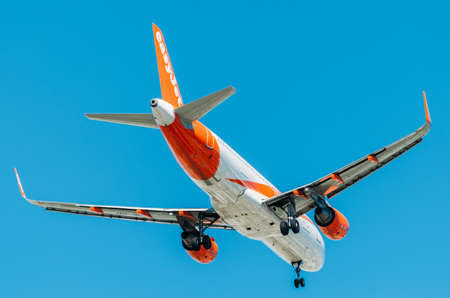 Low cost airliner Easyjet, Airbus A320-214 against blue sky