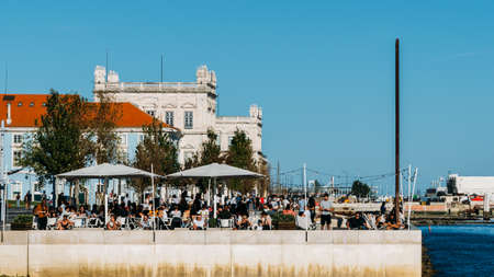 People relaxing at a river-side cafe on the Tejo river in Lisbon, Portugal