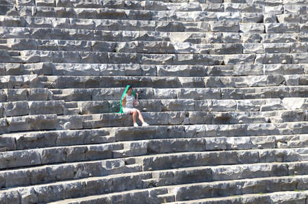 one woman in a green scarf sits on gray stone steps in an ancient amphitheater on a hot summer day Banco de Imagens