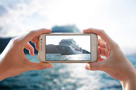 Photo camera of a smartphone. Young woman takes a photo of a cruiser. Фото со стока
