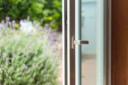 Opened door of a family home. Lock of the sliding door with the yard of background. White PVC door and double glass.
