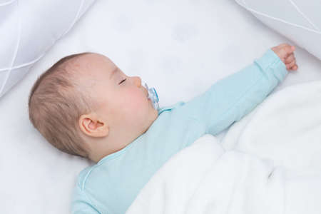 Baby sleeping with open arms in a cradle. Light blue pajama and white bed sheets. A pacifier in his mouth.