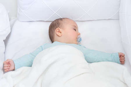 Baby boy sleeping with open arms in a cradle . Light blue pajama and white bed sheets. A pacifier in his mouth.