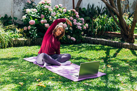Online sport fitness yoga training workout, senior woman in the garden of her home doing exercises on pilates mat opposite laptop at home. Coach in video conference. Healthy lifestyle concept. Stock Photo