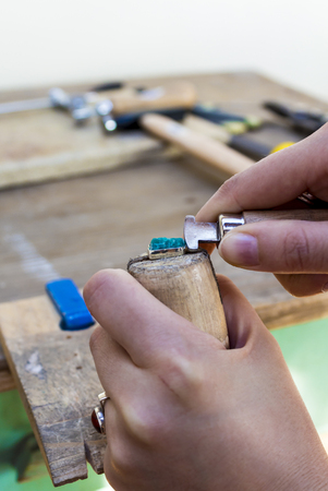 Stonesetting a rough amazonite using a ring clamp Stock Photo